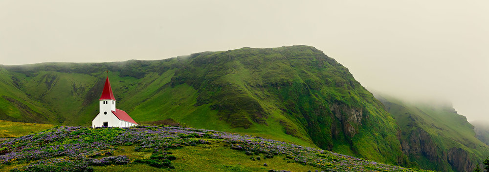 A spectacular panoramic view of the Vik Luthern Church on a hillside above the town. At around 300 inhabitants Vik is the southern most town in Iceland.