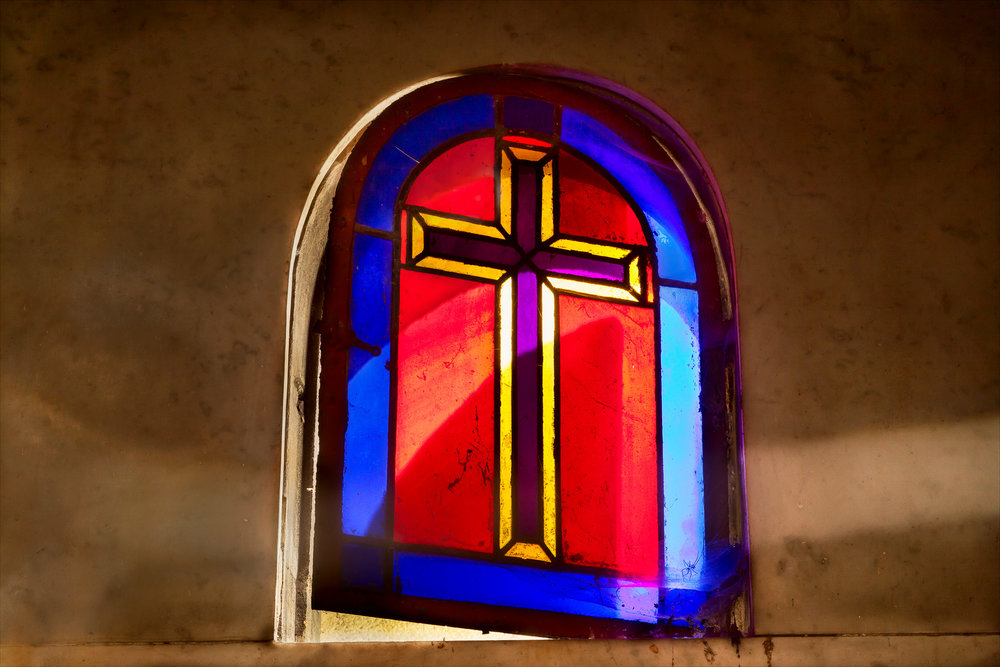 Light passes through a stained glass window, featuring an illustration of the Christian cross, at Père Lachaise Cemetery in Paris, France.