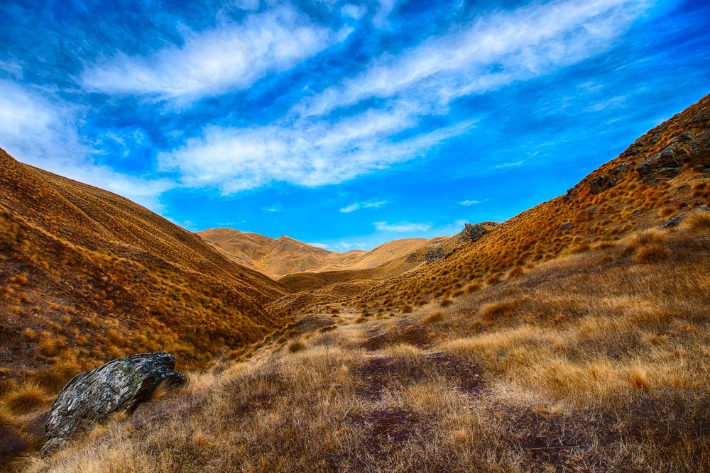 A mountain track over a high country tussock pass on the road between Queenstown and Wanaka, New Zealand.