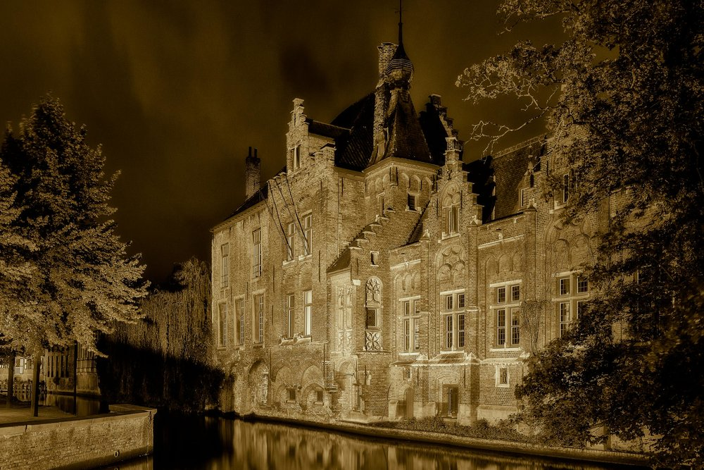 Artificial lights illuminate an historic building on the canal in Bruges, Belgium.