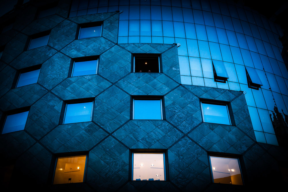 A mix of orange and blue light illuminate a modern building in Vienna, Austria