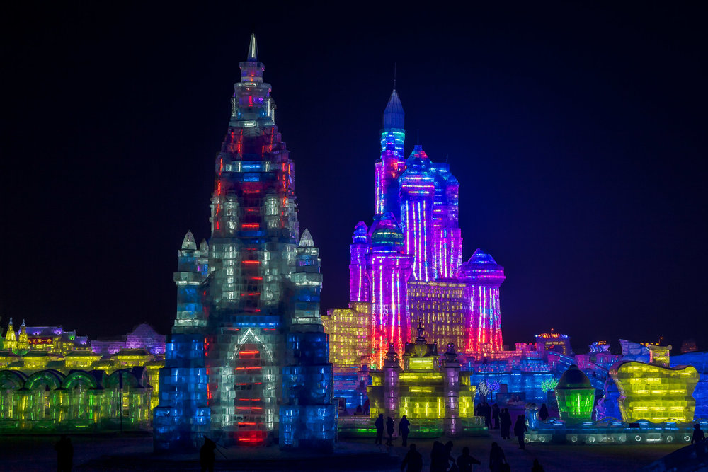 Visitors to the  Harbin Ice and Snow Sculpture Festival  are dwarfed by the size of some of the larger ice sculptures,  lit by neon light ,  at night .