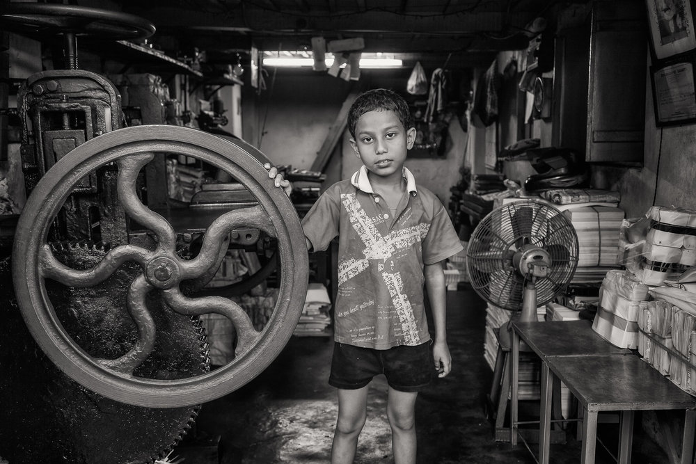 A lovely formal portrait, in black and white, of a young boy in his father's print workshop in Kolkata, India