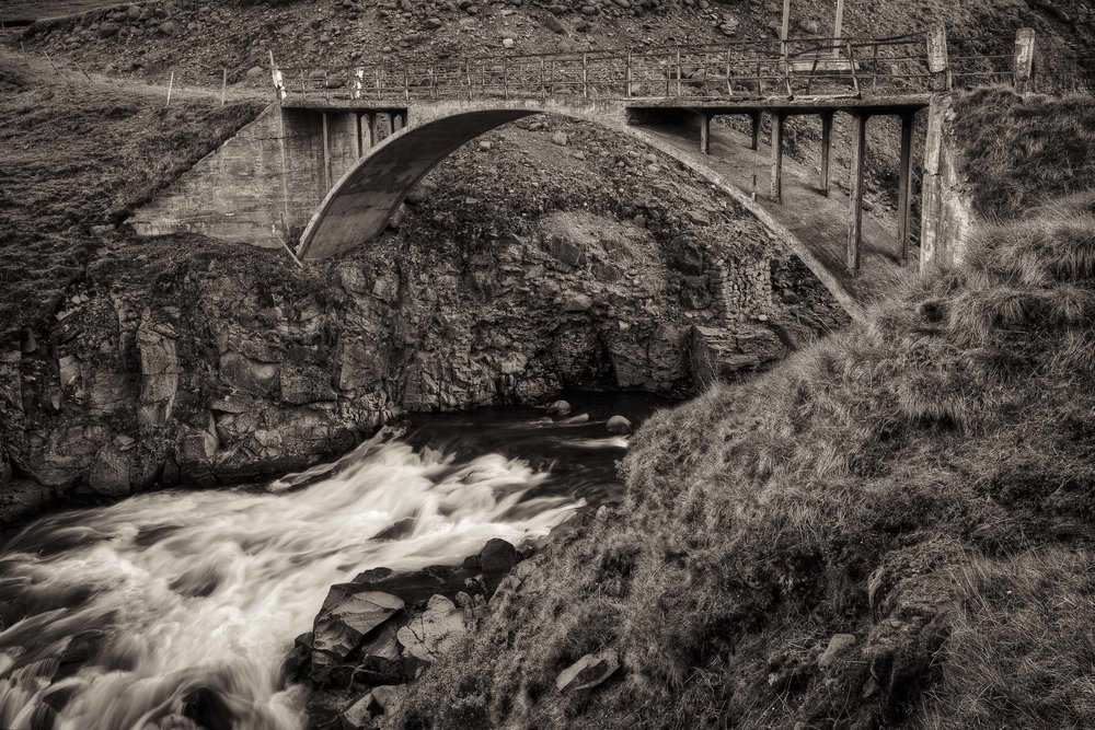 An old stone bridge spanning a fast moving stream in rural Iceland.