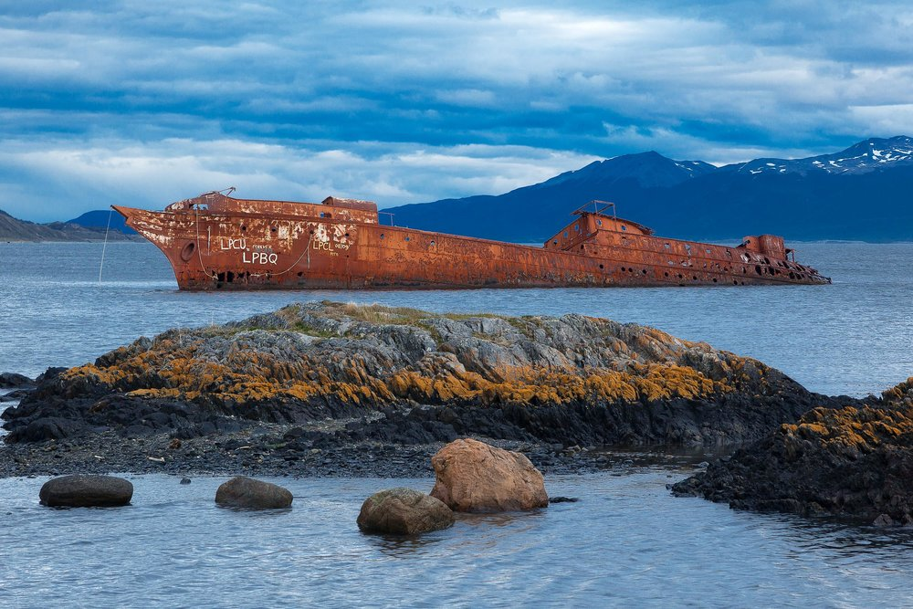 A ship, now no more than a rusting hulk, lies in a bay near the city of Ushuaia in the far south of Argentina. The orange color of the ship is illuminated by the gentle sunlight and is a striking contrast against the predominantly bluish light resulting from gathering storm clouds.