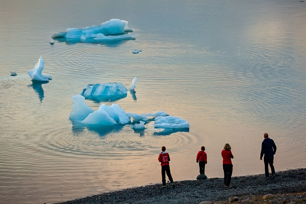 A family watching the breaking up of an iceberg from the shore of the incredible Jökulsárlón Glacier Lagoon in southern Iceland.