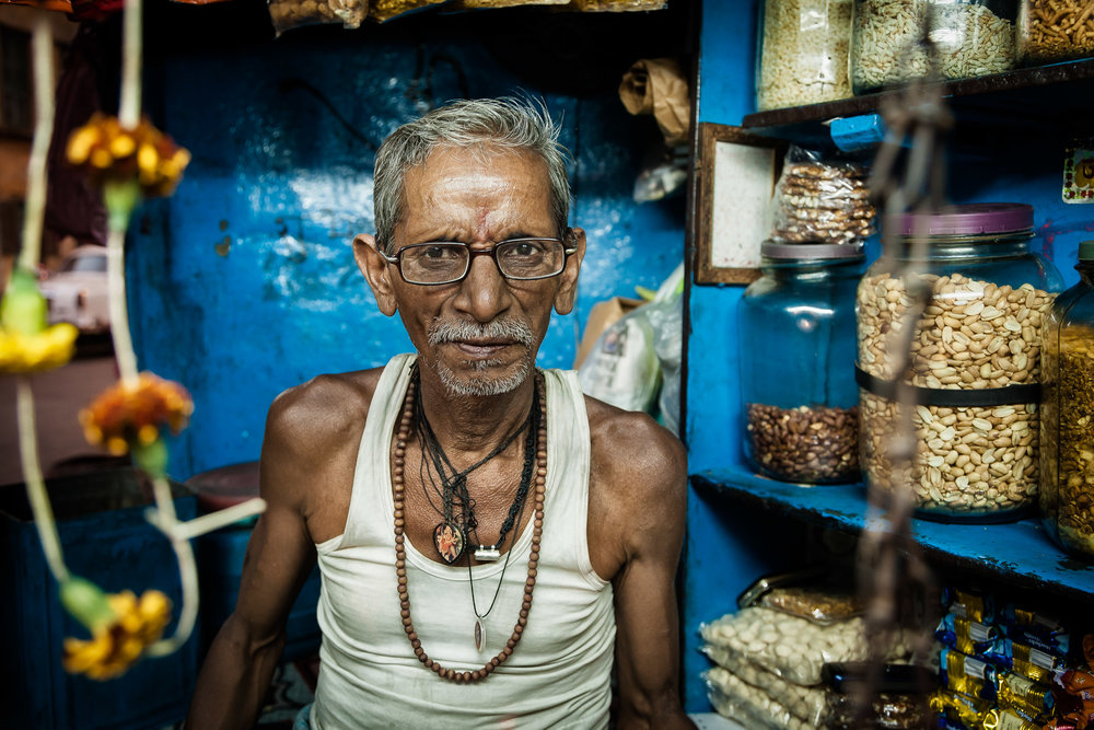 Portrait of a shopkeeper in his tiny, colorful shop in Kolkata, India.