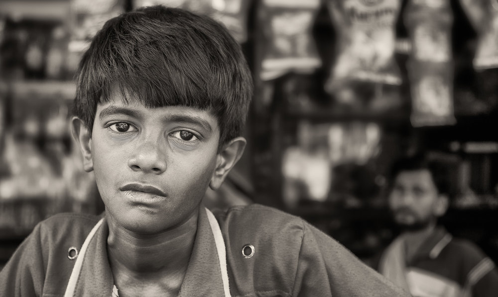 A portrait of a young boy with his father watching on in front of their store in Kolkata, India.