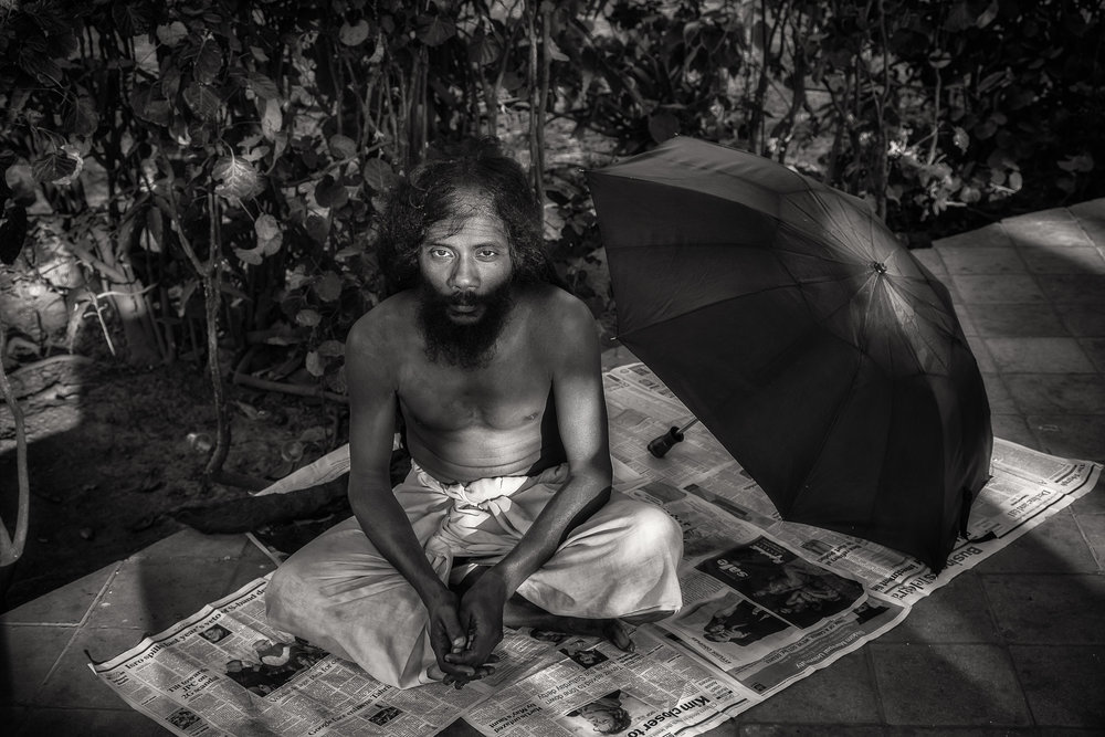 Black and white  portrait of a yogi  resting in the grounds of a temple complex by the banks of the  Hooghly River  in  Kolkata, India .