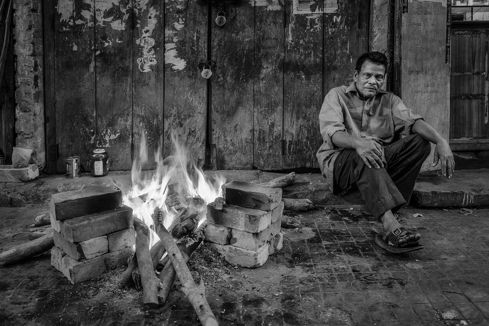 A man sits by a fire in the back streets of Kolkata, India.