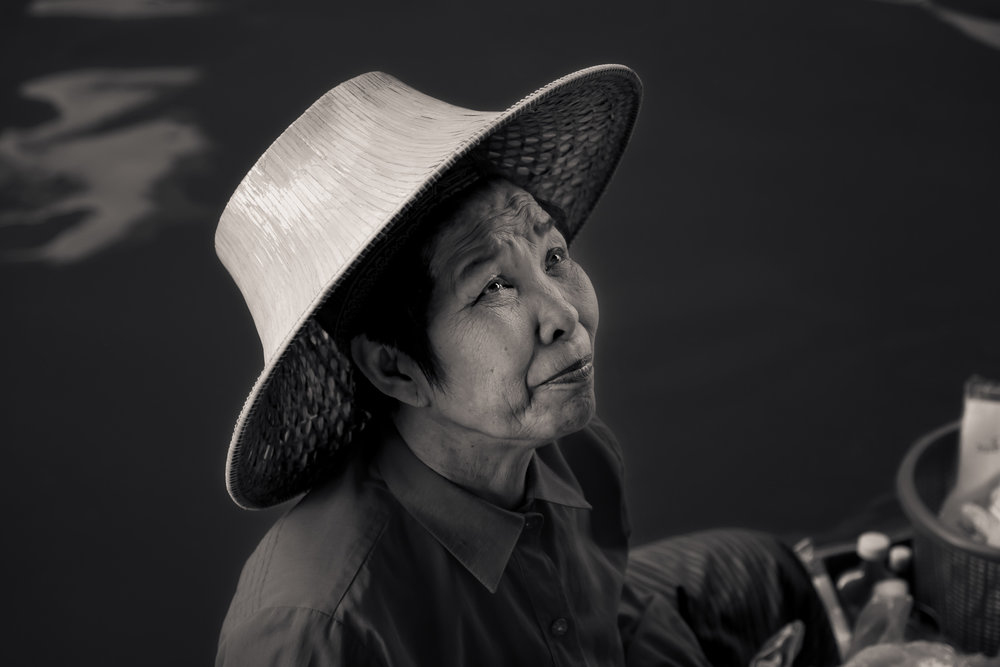 An elderly woman, displaying a trusting expression, at the Floating Markets near Bangkok, Thailand.