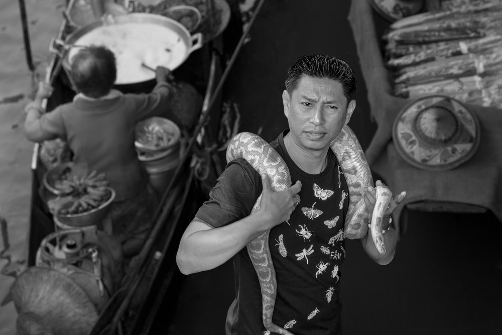 A snake handler poses for photographs with a large, yellow python at the Floating Markets near Bangkok, Thailand.