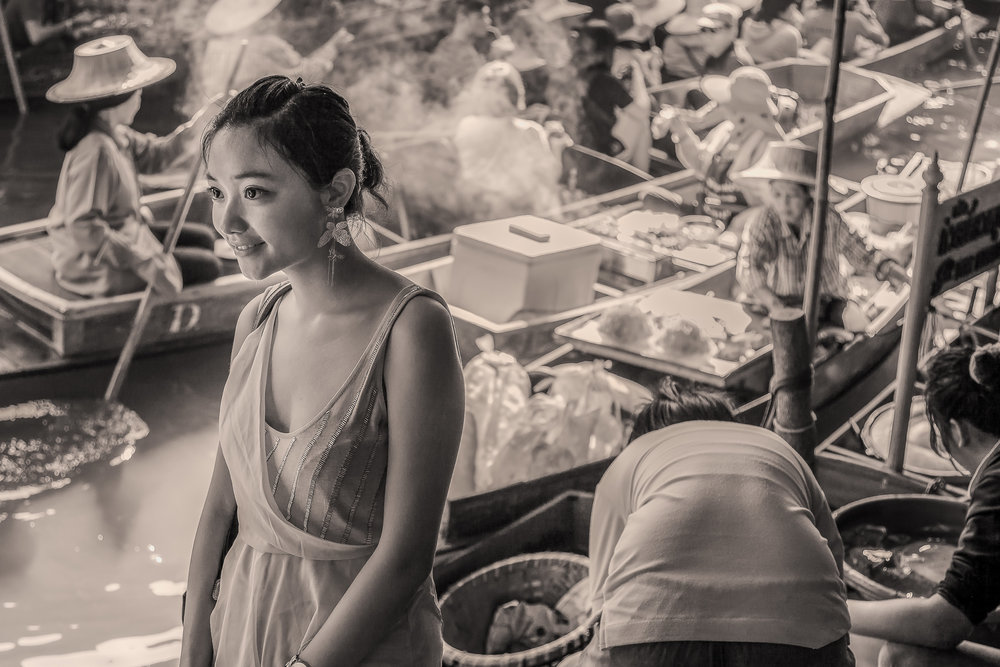 A  young woman  amidst the hussle and bussle of the  Floating Markets  near  Bangkok in Thailand .