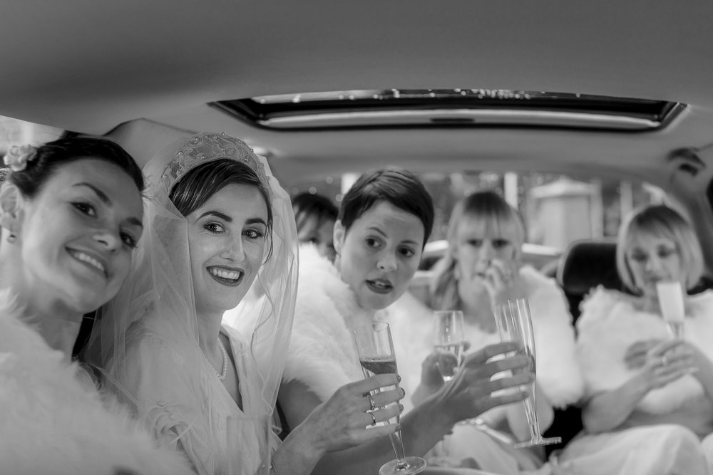 A bride and bridesmaids sipping champagne on their way to the church. Get me to the church, but take your time.