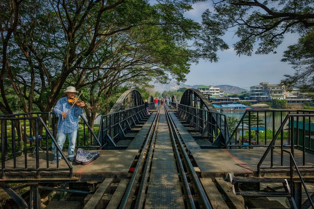 A busker playing violin on the Bridge On The River Kwai near Kanchanaburi in Thailand.