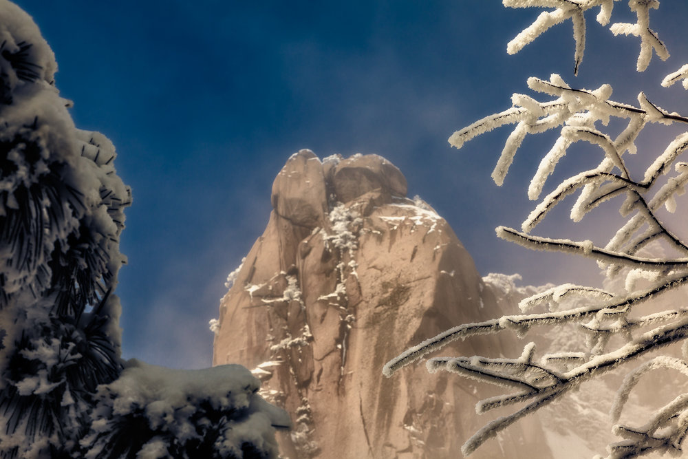 A mountain peak, bathed in warm light, is framed by ice encrusted treees on the spectacular Huangshan (i.e., Yellow Mountain) in China.