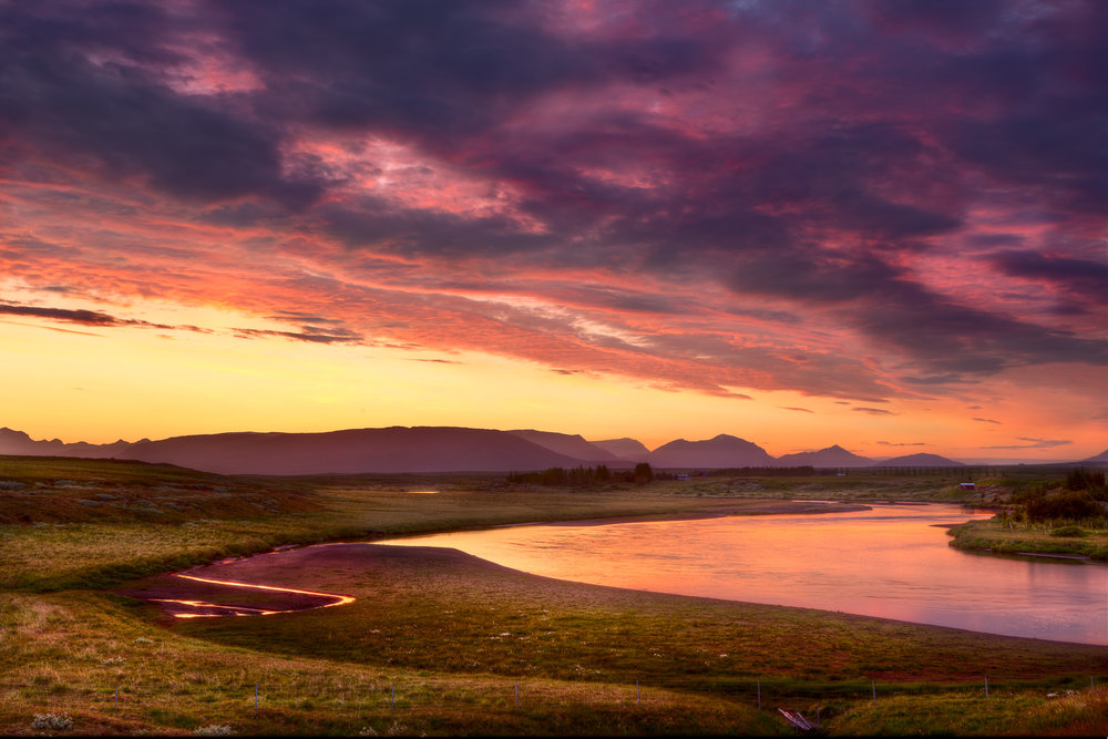 Sunset and a stormy sky reflect light onto a creek and farmland in rural Iceland.