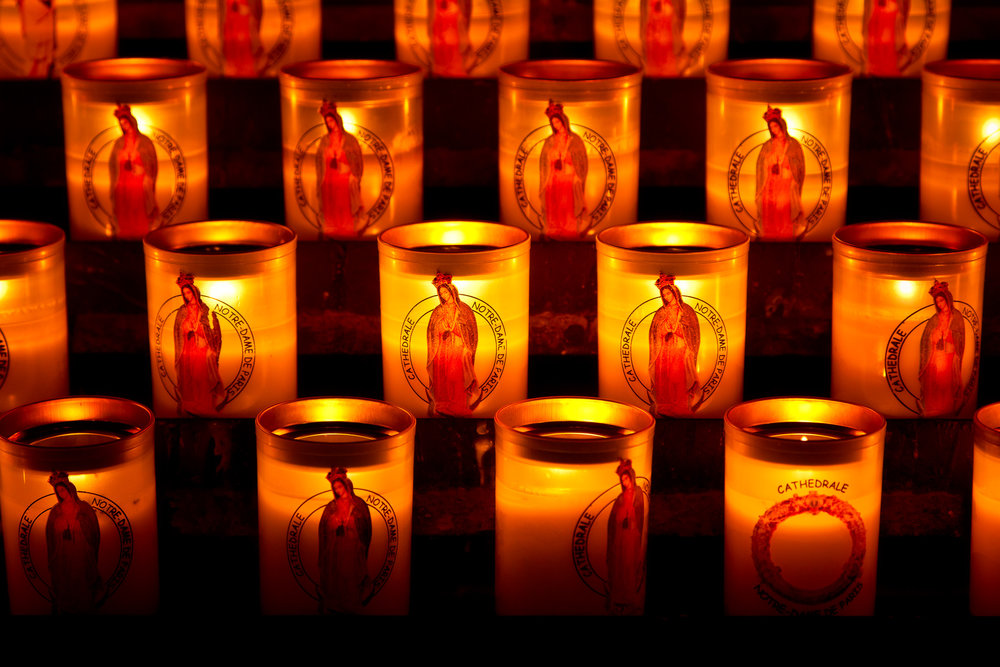 A close up view of  candles , featuring the  Virgin Mary , inside the  Notre Dame Cathedral  in  Paris, France