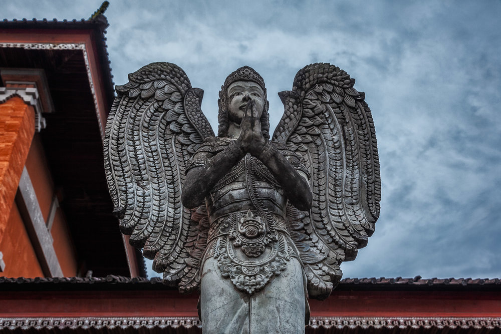 An imposing  staute  pictured against a  stormy sky  in  Bali, Indonesia .