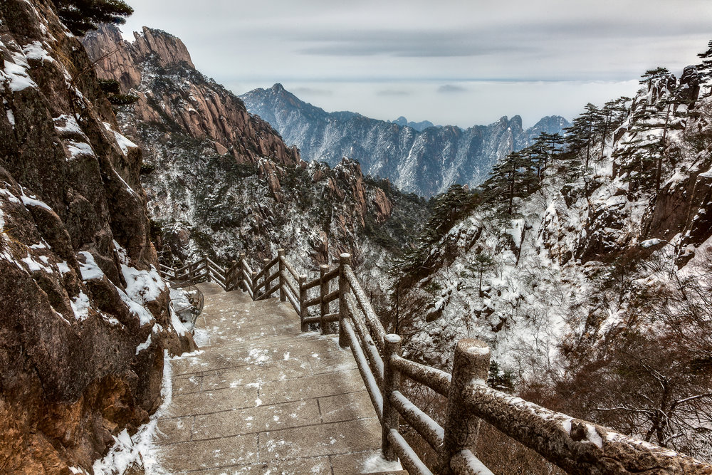A scattering of snow, on and around the mountain trail, on Huangshan (Yellow Mountain), China.