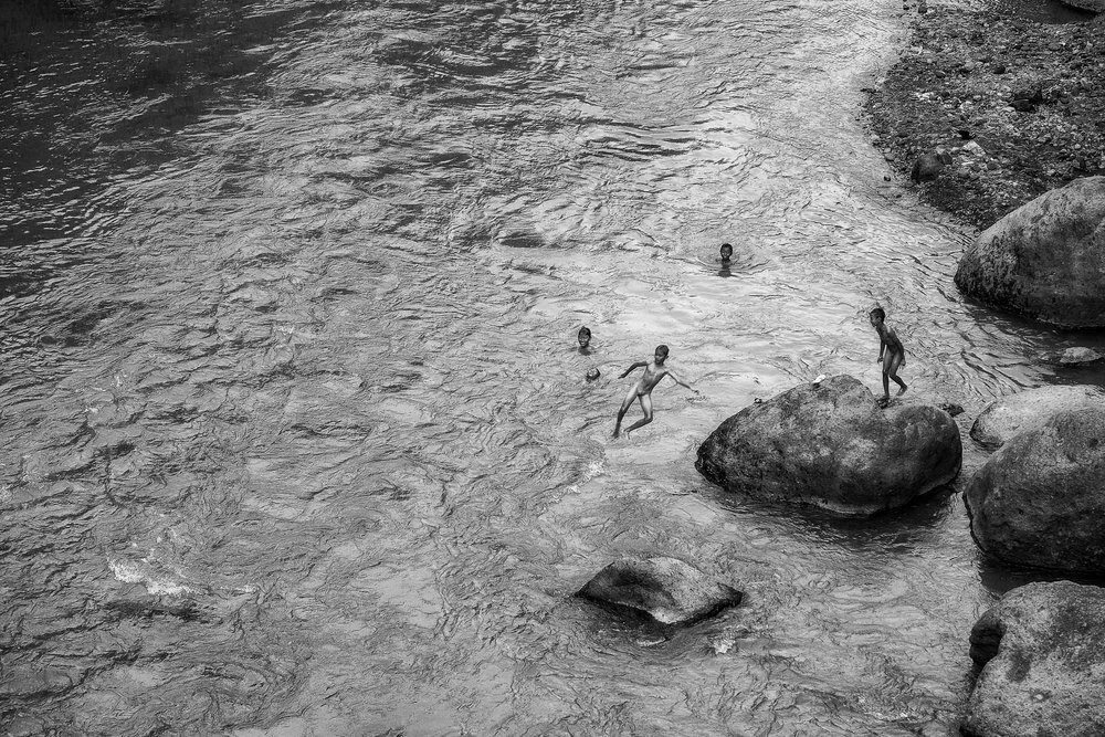 A  group of kids at play  in a river in rural  Bali , Indonesia.