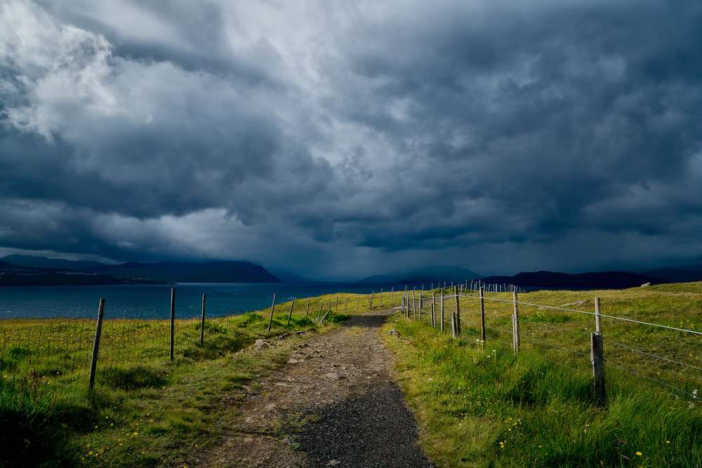 A path leads to the sea , under a stormy sky, at the edge of  Nólsoy  an island 4 km east of the Capital, Tórshavn in the  Faroe Islands .