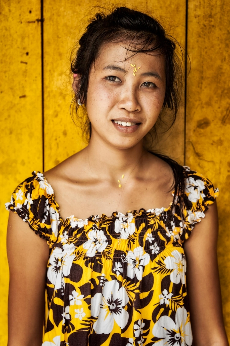 A young Balinese woman dressed in yellow and standing against a yellow painted wall in rural Bali, Indonesia.