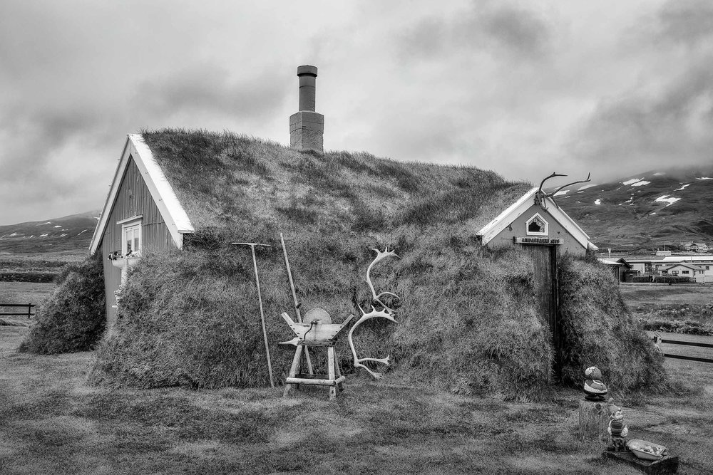 A  black and white rendering  of the famous  Lindarbakki turf house  in the village of  Bakkagerdi  in  Iceland .