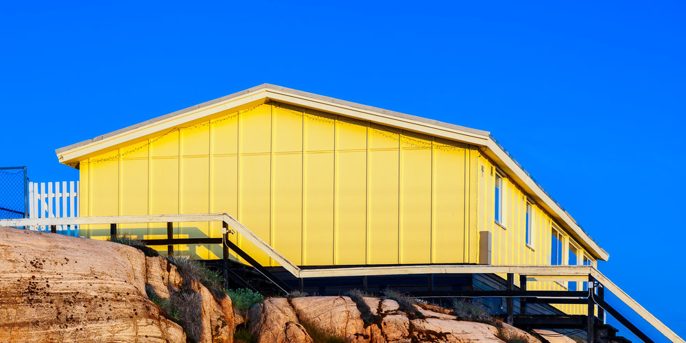 A simple    yellow dwelling   , under a    clear blue sky   , above the    Ilulissat Icefjord    in    Ilulissat, Greenland   .