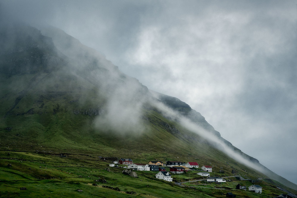 Mist and and rain clouds hover over the village of Kunoy on the island of Kunoy in the Faroe Islands.