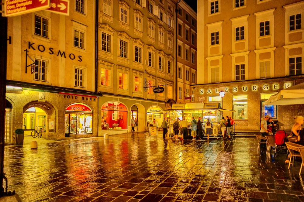People enjoying a drink amidst a vividly lit street scene in the old town of Salzburg on a wet summer's evening.