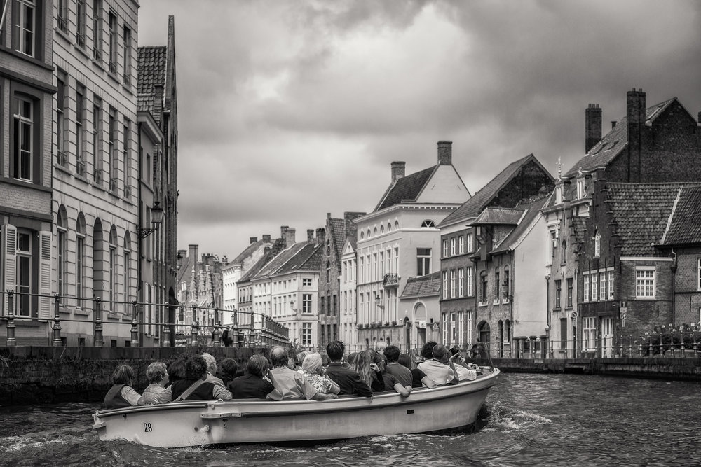 A group of tourists taking a    small boat tour    on the    canal    in    Bruges    (i.e., Brugge),    Belgium   .