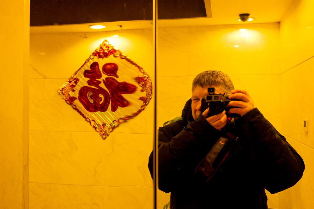 A self portrait of Glenn Guy, the Travel Photography Guru, formed on a shinny set of lift doors in a hotel in Beijing, China.