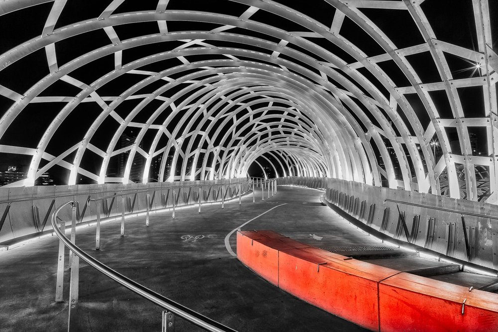 A  red barrier  provides a  splash of vibrant color  in this otherwise black and white photo of  Web Bridge  in the  Docklands  precinct of  Melbourne, Australia .