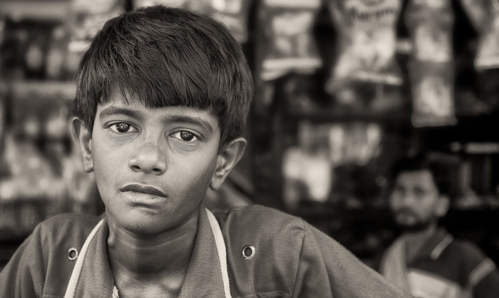 A portrait of a  young boy  with his  father watching on  in front of their store in  Kolkata, India .