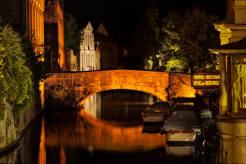 A  quiet night on the canal , lit by  neon light  in  Bruges, Belgium .