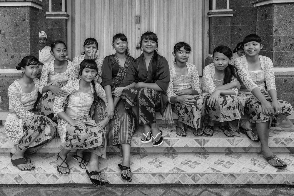 A casual portrait of a group of young women, in traditional dress, in rural Bali, Indonesia.