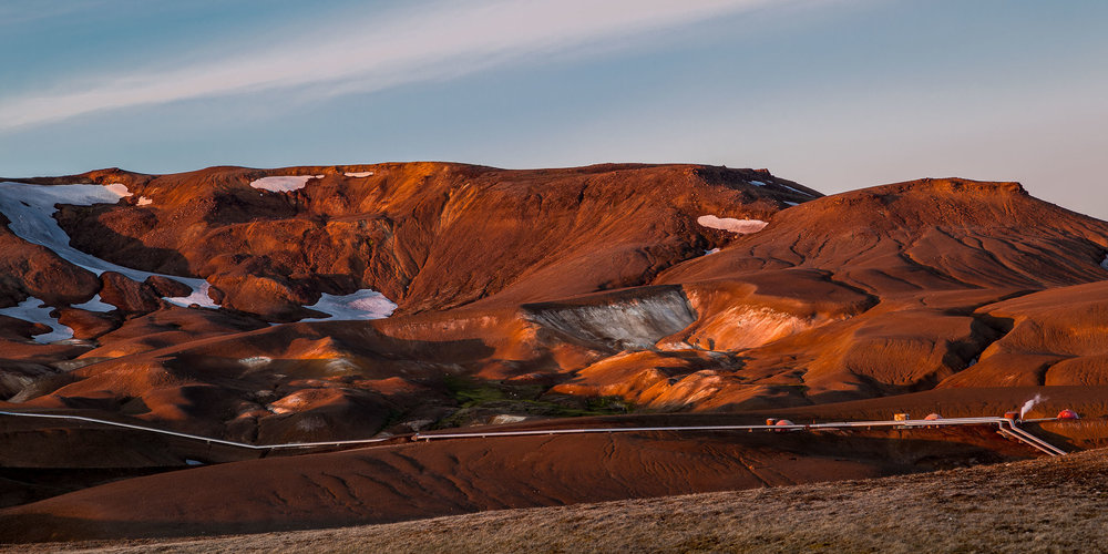 Pipes travel across the landscape at a Geothermal Power Plant at sunset near Myvatn in northern Iceland.