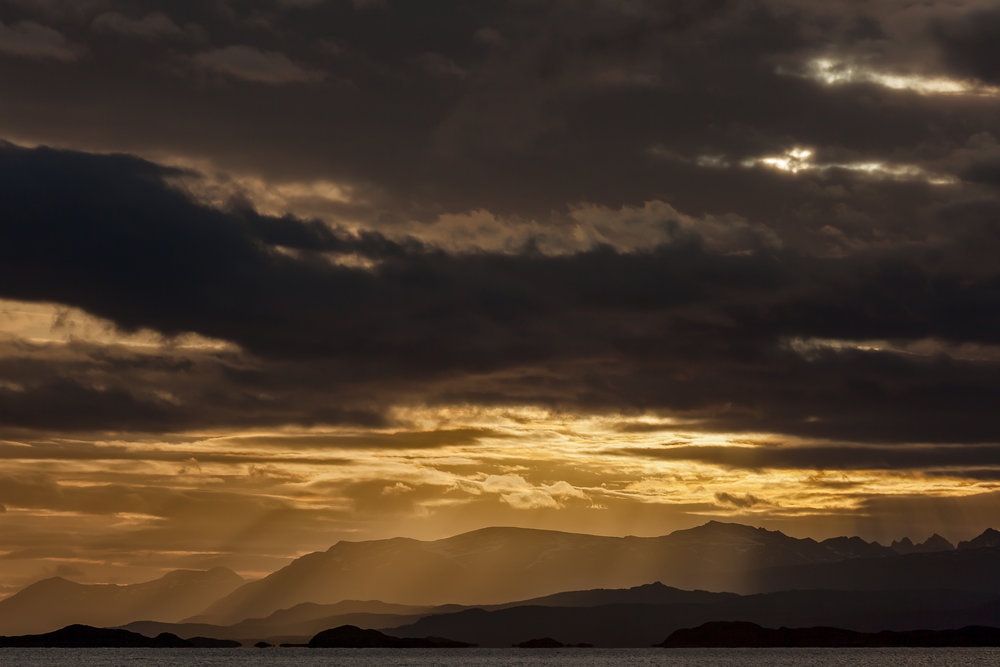 A golden sunrise beneath a stormy sky in Ushuaia, Argentina.