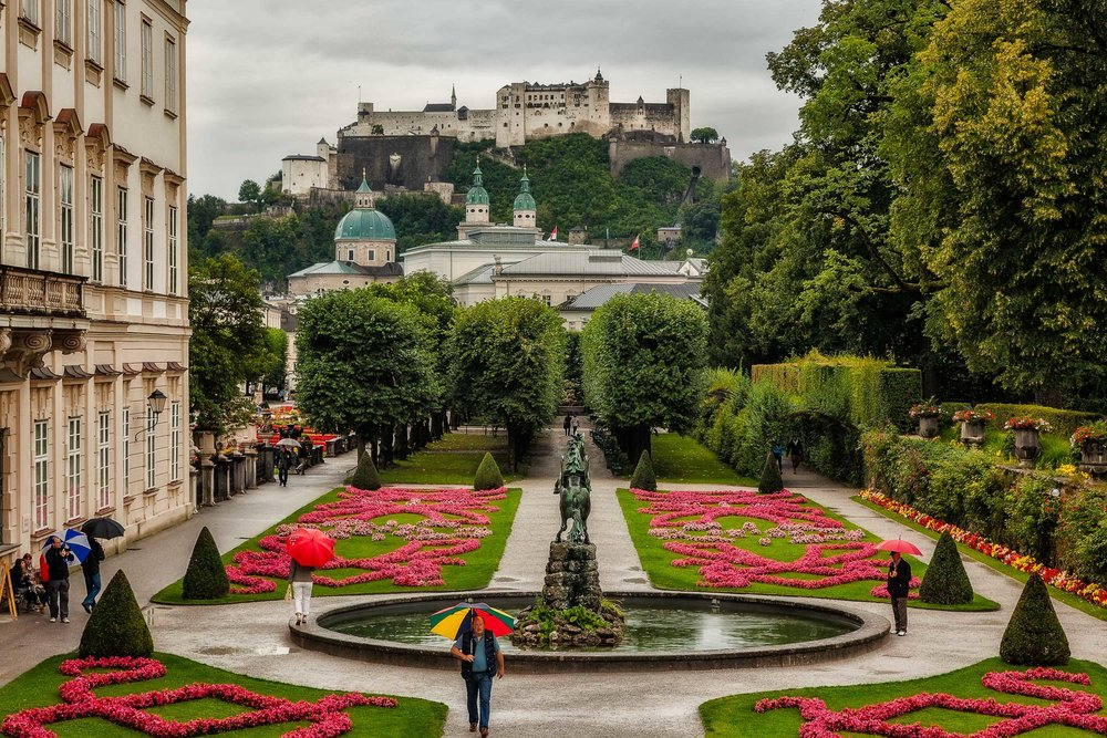 Rain doesn't disturb tourists moving through  Mirabell Gardens  with the impossing  Hohensalzburg Castle  in the background.