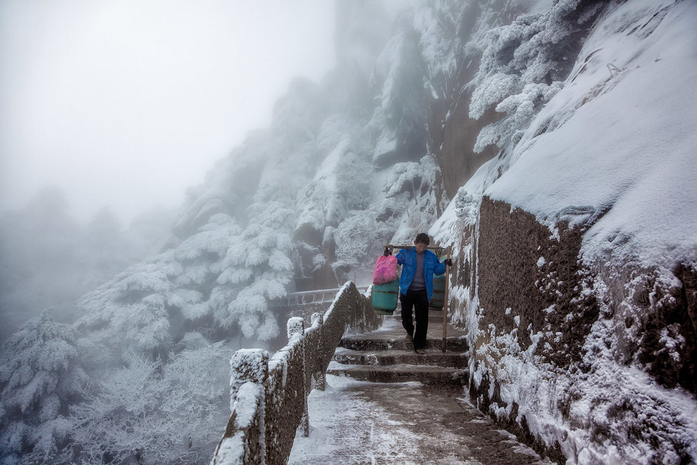 A porter, loaded with goods, walks a windy and exposed path on Huangshan (i.e., Yellow Mountain), China.