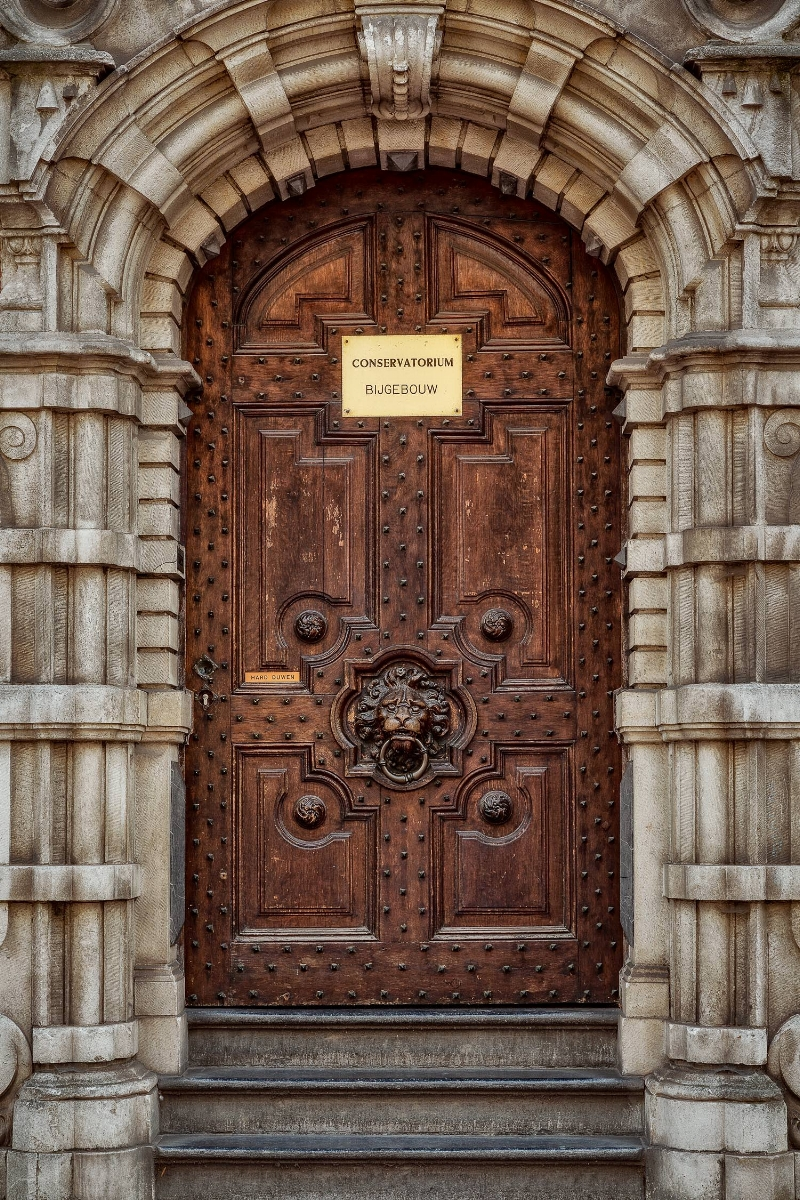 A highly detailed door, beautifully framed in stone, leading into the Conservatorium in Bruges, Belgium.