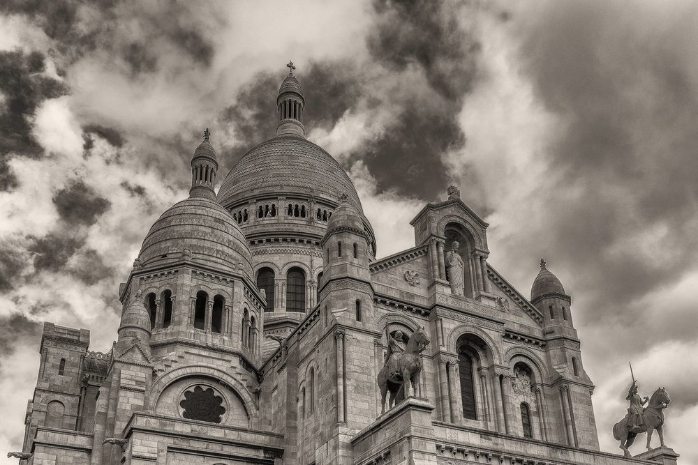 A view up towards the domes and stautes that feature so dominantly on the exterior of the Sacre Coeur Basilica in Paris, France.