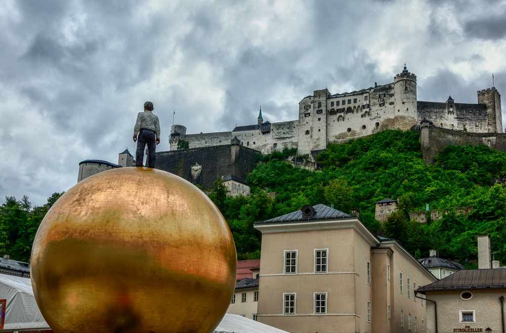 A  brooding sky  and a modern architectural element provides a  dramatic view  of  Hohensalzburg Fortress  in  Salzburg, Austria .