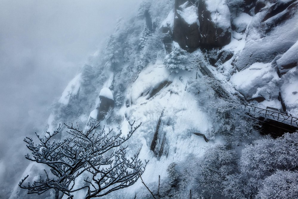 Deep snow    and    encroaching mist    almost hide a path, clinging to the side of the mountain, on    Huangshan    (i.e., Yellow Mountain) in    China    in the    middle of winter   .