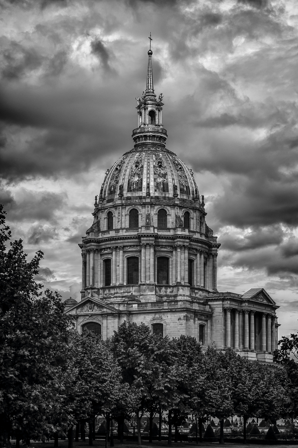 An exterior black and white rendering of  Les Invalides  pictured against a  dramatic sky  in  Paris, France .