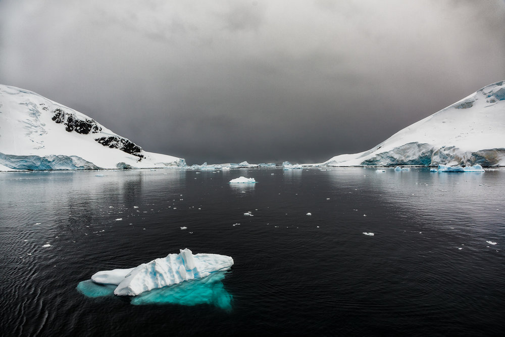 An    iceberg    floats on the    tranquil waters    off    Cuverville Island    in    Antarctica   .
