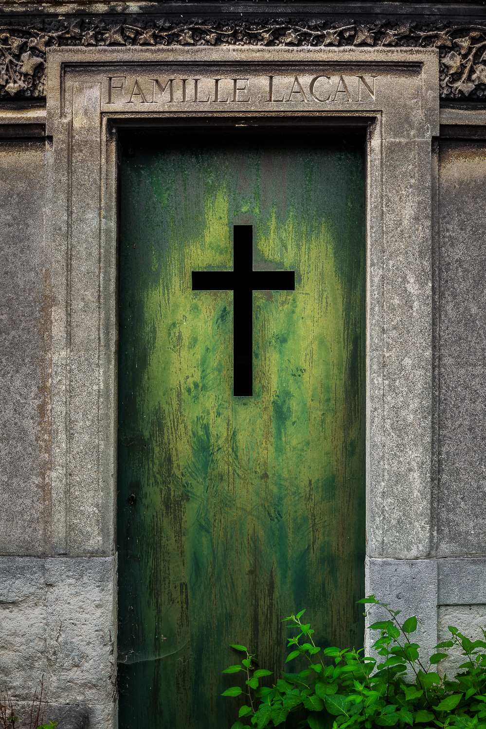 A  christian cross  adorning the  doorway  to a  crypt  at  Pere Lachaise Cemetery  in  Paris, France .