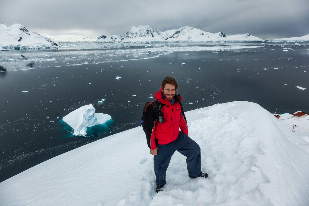 Terry , our barman from  Aurora Expeditions Polar Pioneer , on a hilltop above  Paradise Harbour  in  Antarctica .