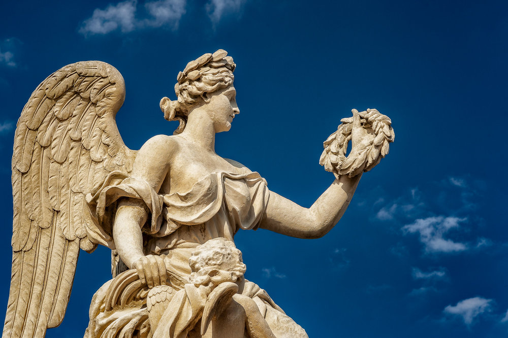 A dramatic photo of an    angel statue   , holding a wreath and    illuminated by warm afternoon light against a brilliant blue sky   , in the grounds of the    Palace Of Versailles    near Paris, France.